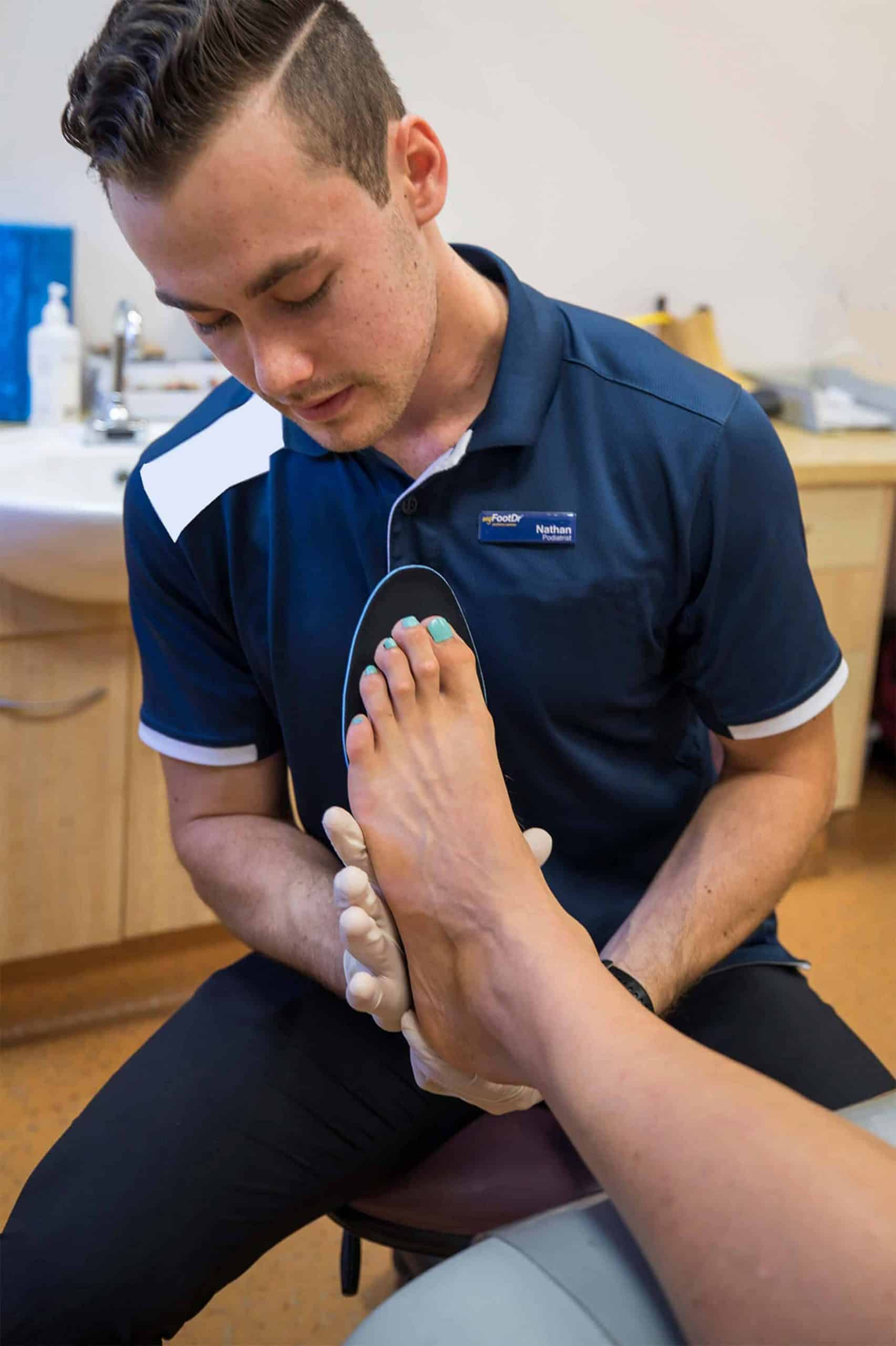 MyFootDr staff checking a patient's foot for custom foot orthotics