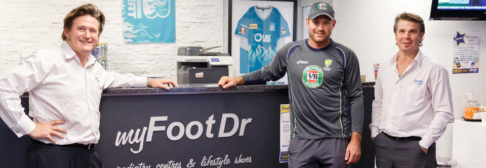 Custom Cricket Shoes - Ryan Harris posing a photo with 2 MyFootDr staff