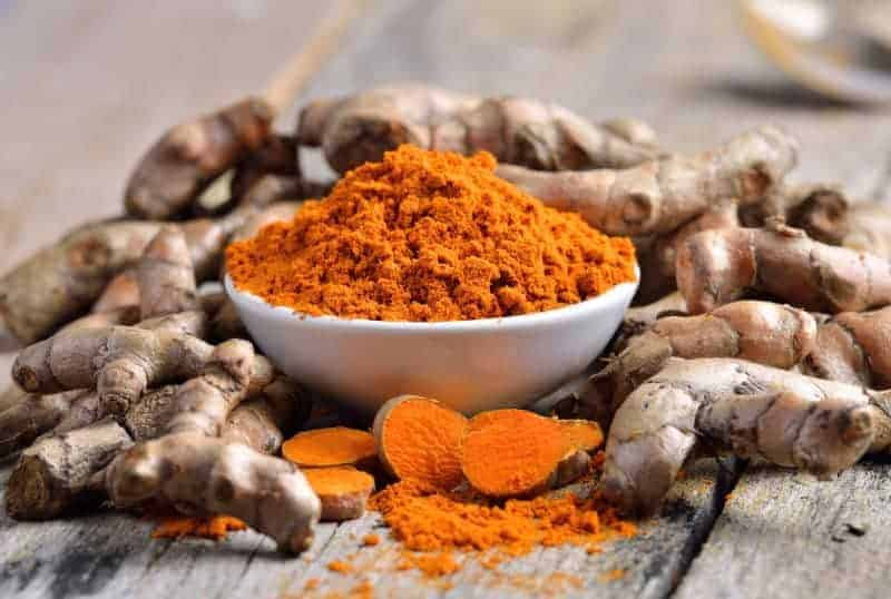 turmeric powder in white dish on wooden background, treatments for achilles tendon injuries