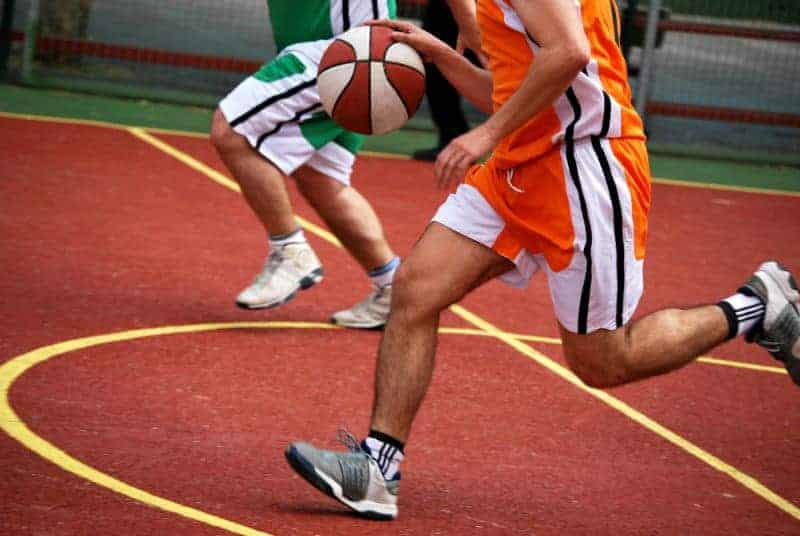 Basketball player running with ball in hand in the court