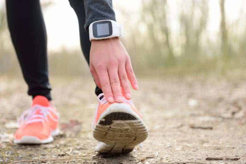 Runner stretching leg before run with smartwatch