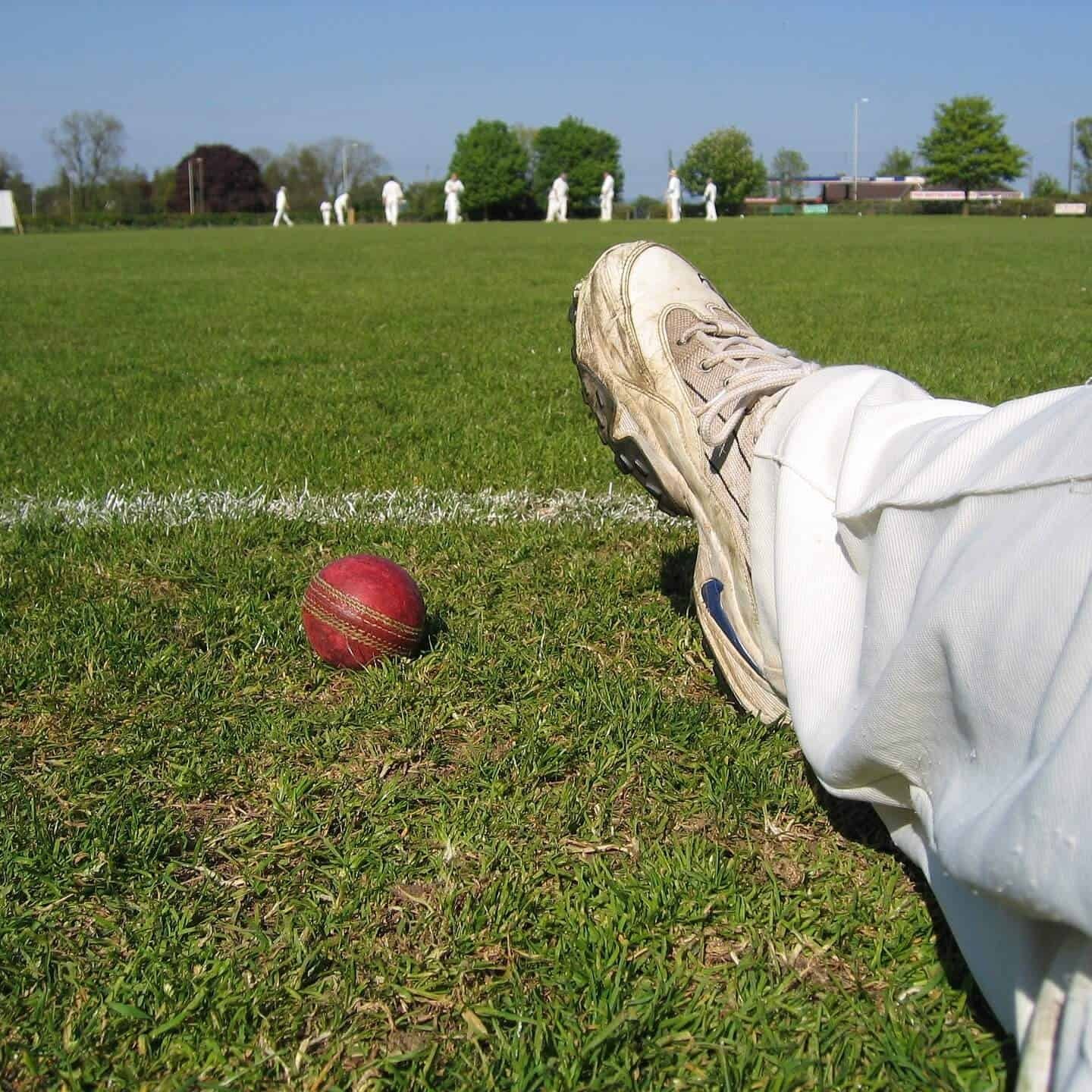 A Cricket Player sitting at one corner with a ball beside him