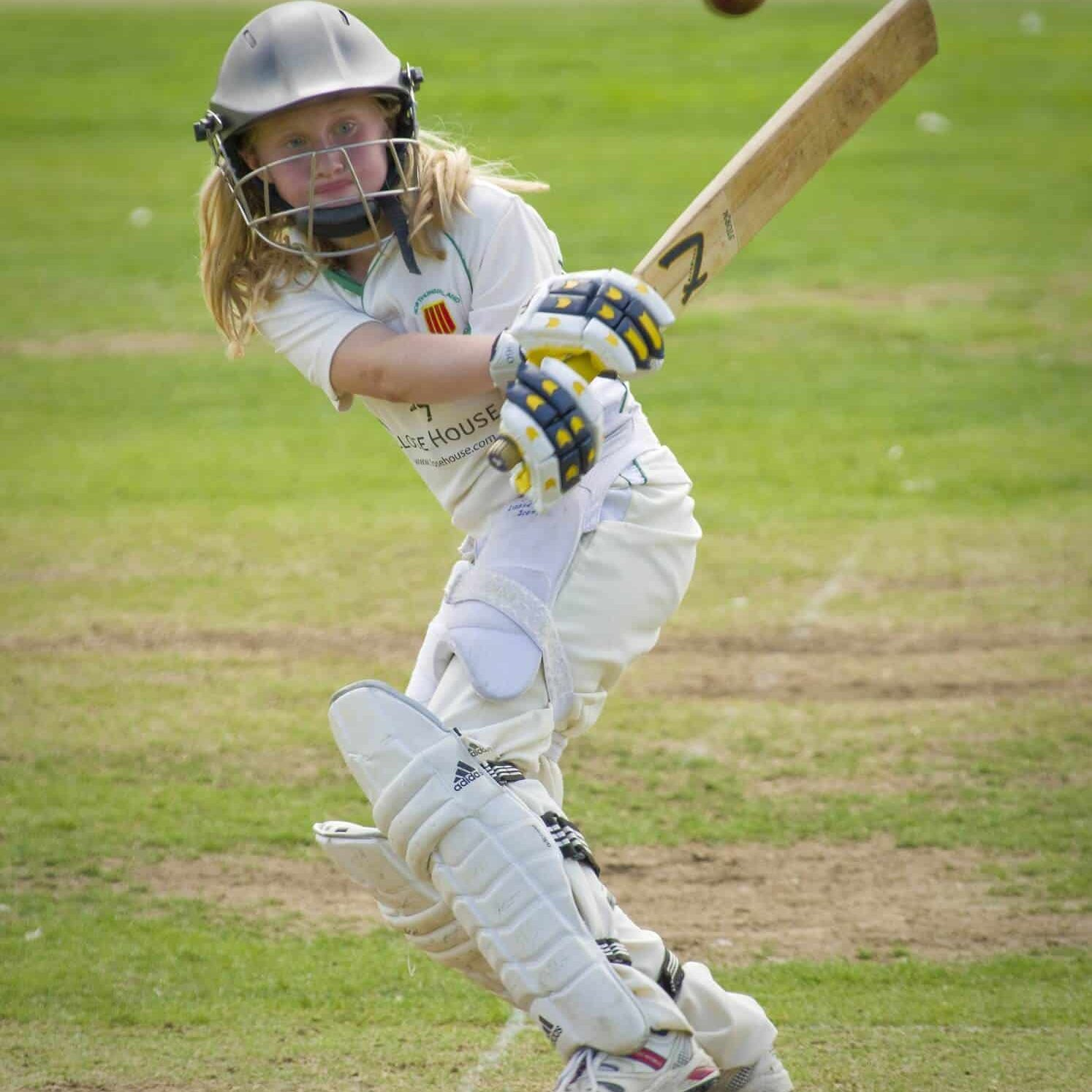 A Cricket Player hitting the ball with her bat