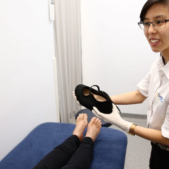 Fall Prevention - MyFootDr podiatrist showing her patient a customised footwear