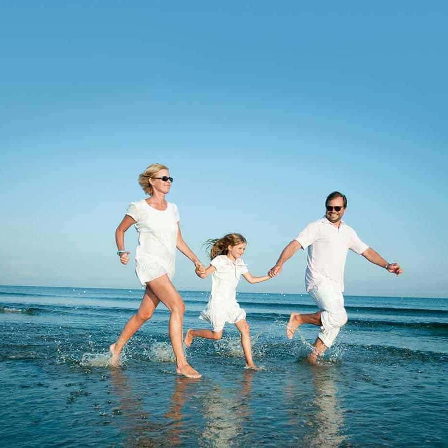 a family running on the beach